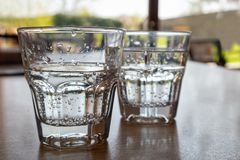 Deux verres fraîchement versés de l'eau de scintillement sur la table en bois Photo libre de droits