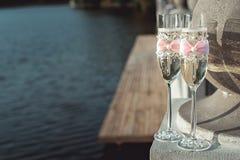 Deux verres les épousant de champagne avec un arc sur une balustrade en pierre Promenade de lac au coucher du soleil Photos stock
