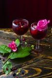 Deux verres pleins de la boisson rouge avec les baies, la glace et un flowe rose photo stock