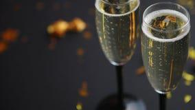 Deux verres pleins du vin de scintillement de champagne avec la décoration d'or clips vidéos
