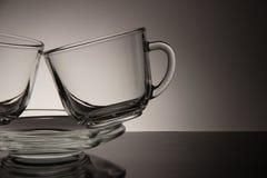 Deux verres pour le thé et une soucoupe vide sur un fond noir Photos stock