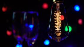 Deux verres que le champagne sont sont allumés dans la perspective du fond voyant de lampes-torches d'ampoules Fin vers le haut clips vidéos