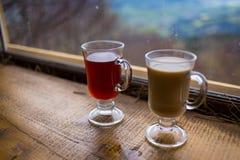 Deux verres, tasse de rouge et boisson chaude de lait couples buvant la Co chaude Photos stock