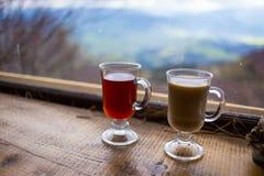 Deux verres, tasse de rouge et boisson chaude de lait couples buvant la Co chaude Image libre de droits