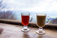 Deux verres, tasse de rouge et boisson chaude de lait couples buvant la Co chaude Photographie stock