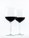 Deux verres transparents exquis avec le vin rouge sur un fond blanc Image libre de droits