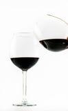Deux verres transparents exquis avec le vin rouge - un vin de versement dans l'autre - sur un fond blanc Photo libre de droits