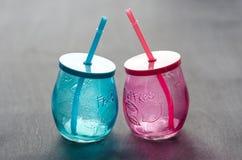 Deux verres vides, faits de verre bleu et rouge avec des pailles Photos libres de droits