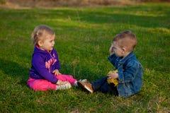 Deux-vieilles années de garçon et fille plaing sur le verre au printemps Photos libres de droits