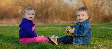 Deux-vieilles années de garçon et fille plaing sur le verre au printemps Image stock