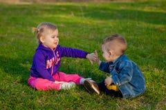 Deux-vieilles années de garçon et fille plaing sur le verre au printemps Photo stock