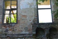 Deux vieilles fenêtres cassées dans le château Image stock