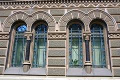 Deux vieilles fenêtres sur un mur gris d'une maison en pierre Photographie stock
