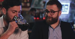 Deux vieux amis buvant de la bière pression et parlant dans la barre de sport Amis s'asseyant au compteur de barre, bière potable banque de vidéos
