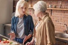 Deux vieux amis féminins communiquant dans la chambre de cuisinier Photographie stock libre de droits