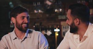 Deux vieux amis heureux buvant de la bière pression et parlant dans la barre de sport Amis s'asseyant au compteur de barre, bière banque de vidéos