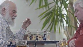 Deux vieux amis jouant la séance d'échecs à la maison Voisins caucasiens de vieux hommes jouant aux échecs joyeux à l'intérieur I clips vidéos