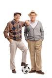 Deux vieux amis posant avec un football Photos stock