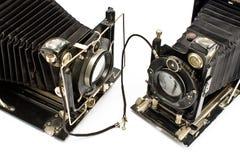Deux vieux appareils-photo retenant des mains Images stock
