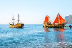 Deux vieux bateaux en bois L'un d'entre eux avec les voiles rouges est sur le pilier images stock