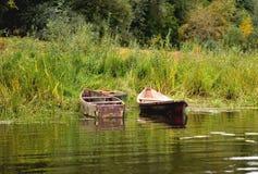 Deux vieux bateaux sur le rivage sont attachés à une vieille roue de voiture, sur un fond d'herbe verte images libres de droits