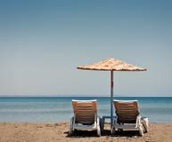 Deux vieux chaises de plage et parapluies de soleil Photo stock