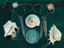 Deux vieux ciseaux énormes de couleur noire sur le fond bleu-foncé parmi des coquilles de mer blanche et cadrans d'une montre de  Photos libres de droits