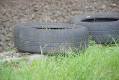 Deux vieux pneus de voiture négligés le long de la route Photo stock