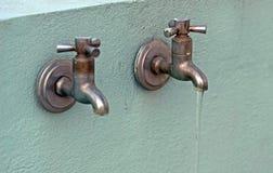 Deux vieux robinets rouillés avec de l'eau découlant d'un image libre de droits