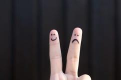 Deux visages tirés par la main d'émoticône sur doigts de personnes Image libre de droits