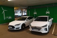 Deux voitures électriques chargeant dans la maison de stationnement photos libres de droits