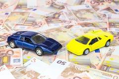 Deux voitures modèles sur d'euro factures Photos stock