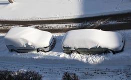 Deux voitures ont couvert la neige dans la rue Images libres de droits