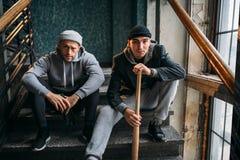 Deux voleurs masculins s'asseyent sur les escaliers images libres de droits