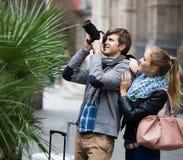Deux voyageurs avec l'appareil photo numérique marchant par la rue de ville Photos stock