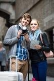 Deux voyageurs avec l'appareil photo numérique marchant par la rue de ville Photo libre de droits
