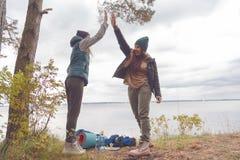 Deux voyageurs d'amies sont fiers d'eux-mêmes et se sont donnés de hauts cinq Le concept du succès d'équipe Photographie stock