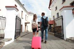 Deux voyageurs des vacances marchant autour de la ville avec le bagage Images stock