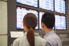 Deux voyageurs regardant des écrans de départ de vol l'aéroport Photos libres de droits