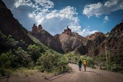 Deux voyageurs vont sur la route de campagne à l'intérieur du canyon Image stock