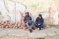 Deux voyous de rue se tenant contre un graffiti ont peint le mur Images libres de droits