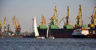 Deux yachts contre le bateau de commerce Photographie stock