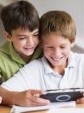 Deux Young Boys jouant avec un jeu vidéo tenu dans la main Image libre de droits