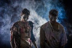 Deux zombis masculins se tenant sur le fond fumeux noir Photo stock