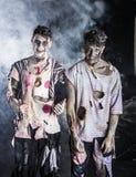 Deux zombis masculins se tenant sur le fond fumeux noir Photographie stock libre de droits