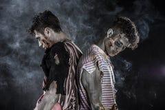 Deux zombis masculins se tenant sur le fond fumeux noir Image stock