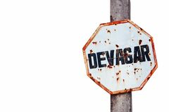 """Devagar"" in Portuguese, slow or slowly written in a rusty and grungy white and red old weathered road traffic sign Royalty Free Stock Photography"