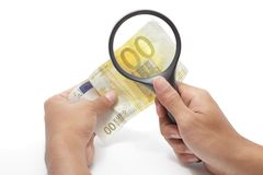 Devaluated euro under scrutiny. Two hands holding a magnifying glass and a devalued euro banknote, highlighting a 00 instead of the 200 euros denomination Stock Photos