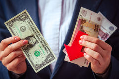 Devaluation. Business person holds roubles, dollars and red arrow. Devaluation of the Russian rouble Royalty Free Stock Photography