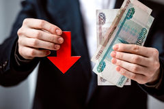 Devaluation. Business person holds roubles and red arrow. Devaluation of the Russian rouble Stock Photo